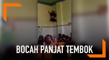 Ketika teman-teman lainnya sibuk belajar, bocah perempuan ini malah diam-diam memanjat tembok di pojokan kelas layaknya Spiderman.