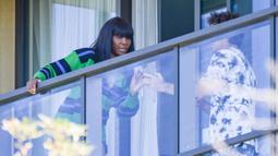 Petenis Amerika Serikat, Venus Williams, melihat hasil foto saat bersantai di balkon hotel di Adelaide, Australia, Jumat (22/1/2021). Venus Williams melakukan karantina selama dua minggu sebelum mengikuti ajang Australia Terbuka 2021. (AFP/Brenton Edwards)