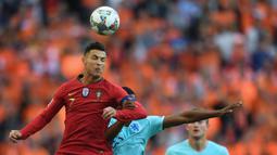 Striker Portugal, Cristiano Ronaldo, duel udara dengan bek Belanda, Denzel Dumfries, pada laga final UEFA Nations League di Stadion Dragao, Porto, Minggu (9/6). Portugal menang 1-0 atas Belanda. (AFP/Patricia De Melo)