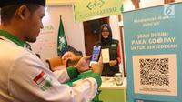 Model mencoba QR Code melalui dompet digital Go-Pay saat peluncuran kerja sama strategis pemberdayaan ekonomi umat berbasis digital di Jakarta (16/7/2019). Gojek, Go-Pay, dan NU Care-LazisNU menjalin kerja sama untuk pembayaran zakat, infaq, dan sedekah secara nontunai. (Liputan6.com/Angga Yuniar)