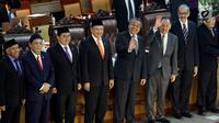 Gubernur BI Perry Warjiyo (empat kanan) bersama mantan Gubernur BI Agus Martowardojo (tiga kanan) melambaikan tangan usai disahkan dalam Rapat Paripurna DPR di Jakarta, Selasa (3/4). Perry  menjadi Gubernur BI periode 2018-2023. (Liputan6.com/JohanTallo)