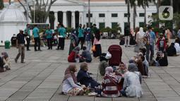 Warga duduk-duduk di kawasan wisata Kota Tua Jakarta, Minggu (4/4/2021). Libur panjang perayaan Paskah 2021 dimasa pemberlakuan PPKM Berskala mikro dimanfaatkan sejumlah warga untuk berwisata di kawasan Kota Tua Jakarta. (Liputan6.com/Helmi Fithriansyah)