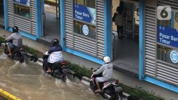 Pengendara motor nekat menerobos genangan banjir di Jalan Gunung Sahari Jakarta, Selasa (25/2/2020). Hujan yang mengguyur Jakarta sejak Senin (24/2) malam membuat sejumlah kali meluap dan menyebabkan banjir. (Liputan6.com/Helmi Fithriansyah)