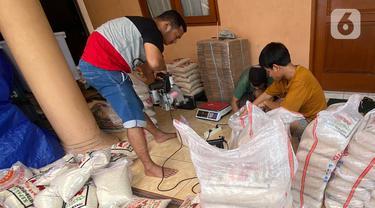 Pekerja melakukan pengemasan beras dalam ukuran 3 Kg dan 5 Kg di kawasan Pisangan Baru, Jakarta Timur, Selasa (20/4/2021). Pengemasan ulang beras 3 kg dan 5 Kg mengalami peningkatan 20% sampai 30% selama seminggu memasuki bulan puasa. (Liputan6.com/Herman Zakharia)