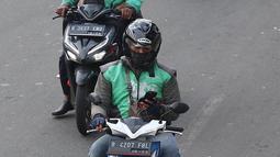 Pengendara sepeda motor mengoperasikan gawainya saat berkendara di Jakarta, Jumat (8/2). Menggunakan GPS saat berkendara dianggap melanggar UU Nomor 22 Tahun 2009 tentang Lalu Lintas dan Angkutan Jalan. (Liputan6.com/Immanuel Antonius)
