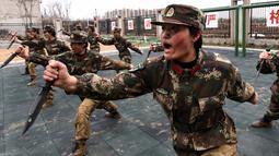 Tentara wanita China berlatih menggunakan pisau saat latihan militer jelang Hari Perempuan Internasional di Hefei, China (6/4). (AFP)