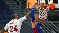 Center Detroit Pistons, Mason Plumlee, melakukan slam dunks melewati guard Toronto Raptors, Norman Powell, pada laga NBA yang digelar Kamis (4/3/2021) pagi WIB. (AP Photo/Chris O'Meara)