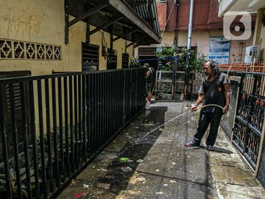 Warga membersihkan jalan usai terendam banjir di permukiman kawasan Kampung Melayu, Jakarta, Selasa (9/2/2021). Banjir yang berangsur surut dimanfaatkan warga untuk membersihkan rumah dan barang-barang dari endapan lumpur. (Liputan6.com/Faizal Fanani)