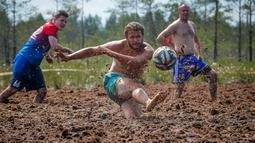 Pemain sepak bola rawa berebut bola dalam turnamen sepak bola rawa di desa Pogy, 60 km (37 mil) dari St. Petersburg, Rusia pada 22 Juni 2019. Meski lumpur menghambat kecepatan atlet, olahraga yang berasal dari Finlandia ini digemari di beberapa negara. (AP/Dmitri Lovetsky)