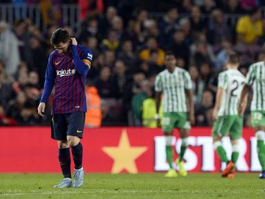 Reaksi Lionel Messi saat Real Betis menciptakan gol ketiga laga lanjutan La Liga 2018/19 yang berlangsung di stadion Camp Nou. Barcelona kalah 3-4. (AFP/Josep Lago)