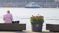 Seorang wanita duduk di samping pot bunga tulip di museum film EYE di Amsterdam, Belanda (8/4/2020). Festival Tulip Amsterdam 2020 menampilkan tulip di jalan-jalan sepanjang bulan April. Akibat epidemi COVID-19, beberapa lokasi pameran tulip ditutup tahun ini. (Xinhua/Sylvia Lederer)