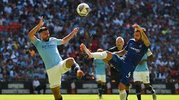 Pemain Manchester City, Sergio Aguero (kiri) berebut bola dengan pemain Chelsea Cesc Fabregas (kanan) dalam Community Shield di Wembley, London, Inggris, Minggu (5/8). Sergio Aguero mencetak dua gol ke gawang Chelsea. (AFP PHOTO/Glyn KIRK)