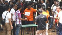 Tersangka insiden penembakan peluru nyasar di ruangan anggota DPR, IAW, menjalani proses rekonstruksi Lapangan Tembak Senayan, Jakarta, Jumat (19/10). IAW dan RMY merupakan Pegawai Negeri Sipil Kementrian Perhubungan. (Liputan6.com/Immanuel Antonius)