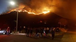 Warga menyaksikan kebakaran hutan dari sudut jalan di West Hills, California, AS, Jumat (9/11). Kebakaran ini dilaporkan telah menewaskan sembilan orang. (AP Photo/Marcio Jose Sanchez)
