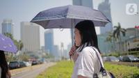 Seorang wanita menggunakan payung selama gelombang panas di Jakarta, Selasa (22/10/2019).  BMKG memprediksi wilayah Indonesia akan mengalami panas selama kurang lebih satu minggu ini. Hal ini dikarenakan matahari yang berada dekat dengan jalur khatulistiwa. (Liputan6.com/Faizal Fanani)