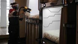 Seorang staf menyemprotkan cairan disinfektan di hotel kapsul Caps Future Rooms, Bogota, Kolombia, 6 Agustus 2020. Sebagai respons terhadap COVID-19, hotel tersebut menerapkan sejumlah langkah keamanan dan sanitasi tambahan. (Xinhua/Jhon Paz)