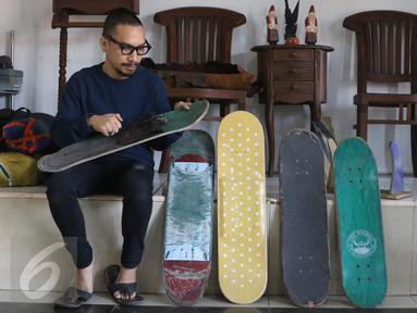 Pemilik brand kacamata kayu Kabau Bonny Andrew memilih sebuah papan skateboard di studio Namines, Jakarta (18/08). Kacamata kayu Kabau Brand lokal asal Jakarta dirintis tahun 2012 di buat dengan papan bekas skateboard.(Liputan6.com/Herman Zakharia)