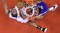 Pebasket Toronto Raptors, Kawhi Leonard, berebut bola dengan pebasket Golden State Warriors, Kevon Looney, pada laga Final NBA di Scotiabank Arena, Toronto, Kamis (30/5). Raptors menang 118-109 atas Warriors. (AP/Nathan Denette)