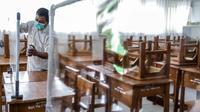 Petugas menyiapkan ruangan kelas yang akan digunakan di SMP N 115 Jakarta, Jumat (21/5/2021). Seleksi PPDB DKI Jakarta tahun ini akan dibagi menjadi empat bagian yakni jalur prestasi, jalur afirmasi, jalur zonasi, dan jalur pindah tugas orangtua dan anak guru. (Liputan6.com/Faizal Fanani)