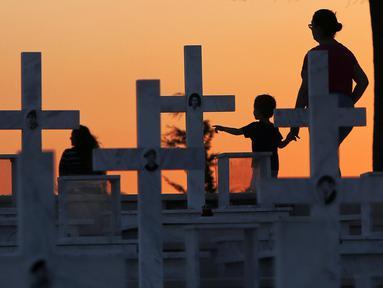 Seorang ibu dan anaknya berjalan dekat kuburan tentara yang tewas dalam invasi Turki ke Siprus di pemakaman militer Tymvos Macedonitissas, Nicosia, Siprus, Senin (20/7/2020). Ribuan orang Yunani dan tentara Siprus tewas selama invasi Turki ke Pulau Siprus pada tahun 1974. (AP Photo/Petros Karadjias)