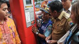 Juru parkir menunjukan cara penggunaan mesin TPE kepada Wagub DKI Jakarta, Djarot Saiful Hidayat, Jakarta, Senin (24/10). Pemprov DKI resmi menerapkan sistem pembayaran parkir pinggir jalan (on street) dengan TPE. (Liputan6.com/Yoppy Renato)