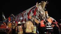 Tim penyelamat dan petugas pemadam kebakaran bekerja setelah sebuah pesawat tergelincir di landasan pacu Bandara Sabiha Gokcen, Istanbul, Turki, Rabu (5/2/2020).  Kecelakaan ini mengakibatkan bandara berhenti beroperasi. (Can Erok/DHA via AP)
