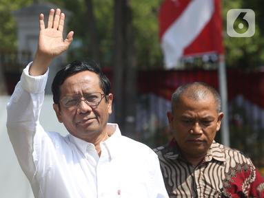 Mantan Ketua Mahkamah Konstitusi Mahfud MD melambaikan tangan saat tiba di kompleks Istana, Jakarta, Senin (21/10/2109). Kedatangan Mahfud MD berlangsung jelang pengumuman menteri Kabinet Kerja Jilid II oleh Presiden Joko Widodo atau Jokowi. (Liputan6.com/Angga Yuniar)