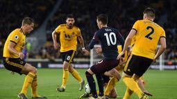 Mesut Ozil dikawal ketat oleh empat pemain Wolves pada laga lanjutan Premier League yang berlangsung di Stadion Molineux, Wolverhampton, Kamis (25/4). Arsenal kalah 1-3 kontra Wolves. (AFP/Paul Ellis)