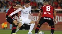 Gelandang Real Madrid, James Rodriguez, berusaha melewati kepungan pemain Real Mallorca pada laga La Liga Spanyol di Stadion Iberostar, Mallorca, Sabtu (19/10). Mallorca menang 1-0 atas Madrid. (AFP/Javier Reina)