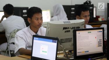 Pelajar mengikuti Ujian Nasional Berbasis Komputer (UNBK) di SMK Negeri 1, Jakarta, Senin (2/4). Sebanyak 1.485.302 siswa dari 13.054 sekolah menengah kejuruan (SMK) sederajat mengikuti Ujian Nasional (UN). (Liputan6.com/Arya Manggala)