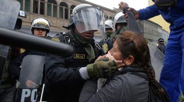 Petugas polisi membantu seorang guru yang terkena gas air mata saat unjuk rasa di Lima, Peru,  (24/8). Sejumlah  Guru sekolah umum menuntut kenaikan gaji. (AP Photo / Martin Mejia)