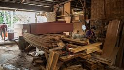 Suasana saat para pekerja menyelesaikan pembuatan peti mati di sebuah bengkel di Surabaya, Jawa Timur, Senin (25/1/2021). Jumlah kematian akibat COVID-19 di Indonesia meningkat lebih dari 28.000. (Juni Kriswanto/AFP)