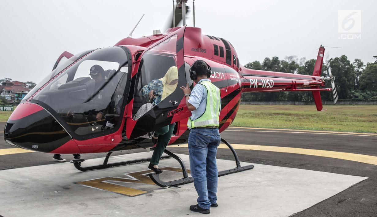 Pemudik turun dari Helikopter jenis Bell 505 di Bandara khusus Wiladatika, Cibubur, Jakarta, Senin (3/6). Untuk musim mudik tahun 2019 ini Heli City melayani 30 penerbangan mudik ke berbagai daerah di Jawa Barat dengan tarif sekali terbang Rp16 juta hingga Rp18 juta. (Liputan6.com/Faizal Fanani)