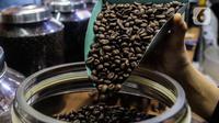 Pekerja memperlihatkan biji kopi dagangannya di salah satu gerai kopi di kawasan Jakarta, Rabu (24/3/2021). Tahun ini pemerintah menargetkan produksi kopi nasional sebesar 834.750 ton, naik dari tahun lalu sebanyak 769,7 ribu ton. (Liputan6.com/Johan Tallo)
