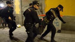 Polisi Spanyol membawa seorang pria saat bentrokan terjadi di Madrid, Spanyol, Kamis (15/3). Bentrokan berawal dari aksi protes imigran atas meninggalnya seorang pedagang jalanan asal Senegal. (AFP Photo/Olmo Calvo)