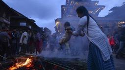 Seorang ibu mengasapi anaknya di sisa pembakaran patung iblis Ghantakarna selama Ghantakarna di kota kuno Bhaktapur, Nepal (30/7/2019). Menurut cerita setempat, setan Ghanta Karna suka menculik anak-anak dan perempuan. (AFP Photo/Prakash Mathema)