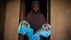 Seorang wanita muslim menggendong saudara laki-laki kembarnya yang berumur 4 hari di depan pintu rumahnya di Igbo Ora, Negara Bagian Oyo, Nigeria pada 3 April 2019.  Igbo Ora, sebuah wilayah di bagian barat daya Nigeria ini terkenal dengan anak-anaknya yang terlahir kembar. (REUTERS/Afolabi Sotunde)