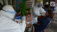 Petugas medis mengambil sampel lendir saat tes usap (swab test) pegawai kecamatan Sawah Besar, Jakarta, Selasa (18/8/2020). Tes swab yang dilakukan terhadap seluruh pegawai kecamatan Sawah Besar itu sebagai upaya memutus mata rantai penyebaran Virus Corona Covid-19. (merdeka.com/Imam Buhori)