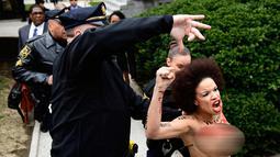 Polisi berusaha menahan pengunjuk rasa wanita yang tampil topless di sidang kekerasan seksual komedian Bill Cosby di Gedung Pengadilan Montgomery, Pennsylvania, Amerika Serikat, Senin (9/4). Wanita terus memaki Bill Cosby. (AP Photo/Corey Perrine)