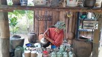 Nyai Fatimah sedang menyeduh kopi di pondok kopi dusun di Desa Muarajambi, Kecamatan Maro Sebo, Muaro Jambi, Jambi. (Liputan6.com/Gresi Plasmanto)