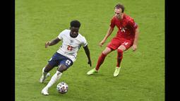 Sembilan menit kemudian, Bukayo Saka yang lolos perangkap offside berhasil menerobos tak terkawal memasuki pertahanan Denmark dan mengumpan bola ke mulut gawang Kasper Schmeichel. (Foto: AP/Pool/Justin Tallis)