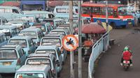 Pengendara sepeda motor melintasi jalur angkutan umum di Terminal Kampung Melayu, Jakarta, Rabu (6/2). Sejumlah pengendara nekat menerobos masuk terminal untuk memotong jalur guna memersingkat waktu tempuh. (Liputan6.com/Immanuel Antonius)