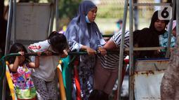 Sejumlah anak dan remaja menikmati Taman Kota Waduk Pluit di Penjaringan, Jakarta Utara, Minggu (27/12/2020). Taman Kota Waduk Pluit dibuka kembali setelah ditutup pada libur Natal, namun banyak warga yang berwisata tidak menerapkan protokol kesehatan. (Liputan6.com/Johan Tallo)