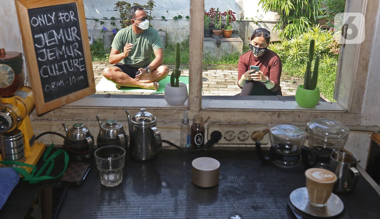 Pelanggan berjemur di halaman kedai kopi Nyambi Ngopi, Depok, Jawa Barat, Selasa (3/8/2021). Kedai kopi tersebut menjadikan halamannya untuk program Ngopi Sambil Berjemur pada pukul 09.00 - 10.00 WIB dengan menerapkan protokol kesehatan. (Liputan6.com/Herman Zakharia)