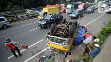 Truk bermuatan puing terbalik akibat salah satu ban belakang lepas di jalan tol Pondok Indah dekat pintu keluar Lebak Bulus, Jakarta, Jumat (29/5/2020). Dalam kecelakaan tersebut tidak ada korban jiwa namun membuat kendaraan yang melintas jalan tol tersendat. (merdeka.com/Dwi Narwoko)
