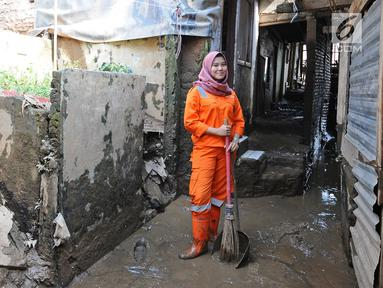Petugas PPSU Kelurahan Kampung Melayu Siti Hajar berpose saat membersihkan sisa lumpur akibat banjir yang melanda Kebon Pala, Jakarta, Kamis (25/4). Siti Hajar (19) merupakan lulusan SMK yang baru 4 bulan bekerja menjadi pasukan oranye. (Liputan6.com/Herman Zakharia)