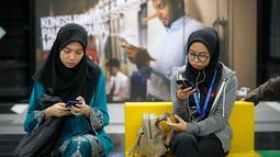 Penumpang menunggu kedatangan kereta dengan latar belakang iklan larangan penyebaran hoax atau berita bohong di Stasiun Kereta Kuala Lumpur, Malaysia, Senin (2/4). Pemerintah Malaysia mengesahkan UU Antihoax jelang Pemilu. (AP Photo/Vincent Thian)