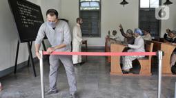 Petugas memasang garis batas pengunjung di salah satu ruangan koleksi Museum Kebangkitan Nasional, Jakarta, Senin (8/6/2020). Pengelola menyiapkan standar protokol kesehatan jelang dibuka kembali untuk umum saat masa PSBB Transisi guna memutus penyebaran Covid-19. (merdeka.com/Iqbal S Nugroho)