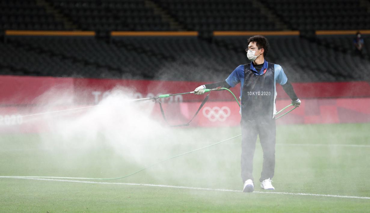 Petugas menyemprotkan disinfektan ke lapangan untuk menghentikan penyebaran virus corona COVID-19 jelang pertandingan sepak bola putaran pertama grup C putra Olimpiade Tokyo 2020 antara Argentina dan Australia di Sapporo Dome, Sapporo, Jepang, Kamis (22/7/2021). (ASANO IKKO/AFP)