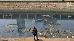 Seorang pria mengamati aliran Kanal Banjir Barat yang berwarna hitam pekat dan dipenuhi tumpukan sampah di Jakarta, Minggu (22/9/2019). Tumpukkan sampah dan aliran air yang berwarna hitam pekat tersebut menimbulkan bau tak sedap. (merdeka.com/Iqbal S Nugroho)